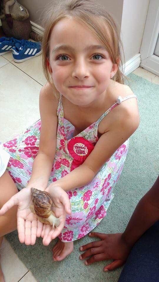 birthday girl holding a giant africal snail at the kids animal party from Animal Club